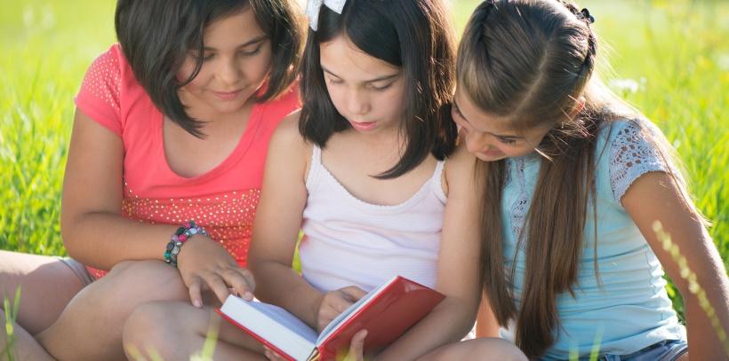 Three happy teen girls reading book at park
